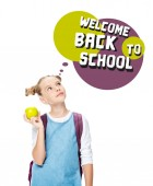 Fotografie schoolchild holding apple and looking up at speech bubble with welcome back to school lettering, isolated on white