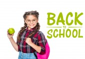 smiling schoolchild with backpack holding apple isolated on white, with back to school lettering
