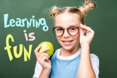 schoolchild holding apple and touching glasses near blackboard, with learning is fun lettering