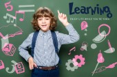 Fotografie schoolboy showing idea gesture near blackboard, with icons and learning - enjoy life while youre yong lettering