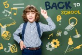 Photo schoolboy showing idea gesture near blackboard, with icons and back to school lettering