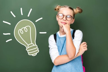 Pensive schoolchild in glasses looking up near blackboard with light bulb sign stock vector