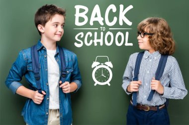 schoolboys with backpacks looking at each other near blackboard, with alarm clock and