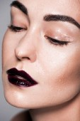 close up portrait of attractive girl with black lips and wet face, isolated on grey