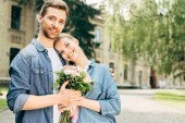 Photo happy young couple holding flower bouquet at park and looking at camera