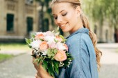 Fotografie smiling young woman looking at flower bouquet
