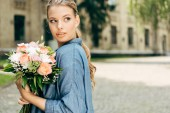 Fotografie attractive young woman with flower bouquet looking away