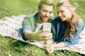 beautiful young couple lying on grass at park and taking selfie