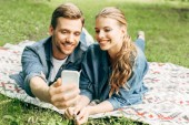 smiling young couple lying on grass at park and taking selfie