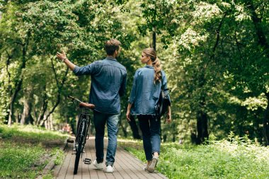 rear view of beautiful young couple in denim shirts with bicycle walking by park