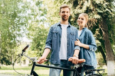 Beautiful young couple with vintage bicycle standing at park and looking at camera stock vector