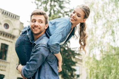 happy young man carrying his girlfriend on shoulder at park