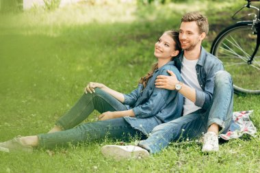 beautiful young couple sitting on grass at park together