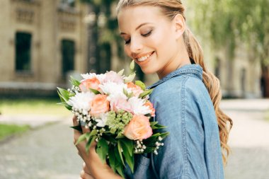 Smiling young woman looking at flower bouquet stock vector