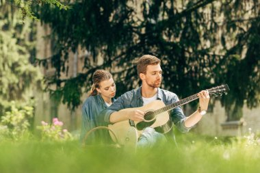 attractive young man playing guitar for his girlfriend during picnic at park