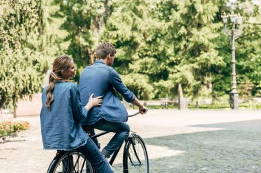 beautiful young couple riding bicycle together at park