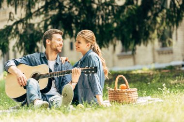 attractive young man playing guitar for his smiling girlfriend during picnic at park