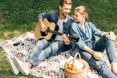 high angle view of handsome young man playing guitar for his smiling girlfriend while relaxing at park