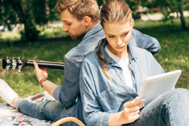 handsome young man playing guitar for his girlfriend while she using tablet on grass at park