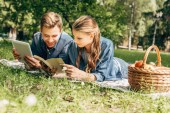 happy young couple lying on grass at park with tablet and book