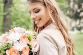 Fotografie close-up portrait of happy young woman looking at flower bouquet