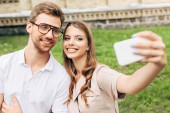 beautiful young couple taking selfie in front of green grass