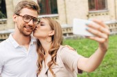 beautiful young couple taking selfie while spending time together near old building