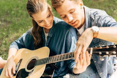 close-up shot of young happy woman learning to play guitar with boyfriend at park
