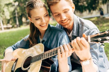 close-up shot of young smiling woman learning to play guitar with boyfriend at park