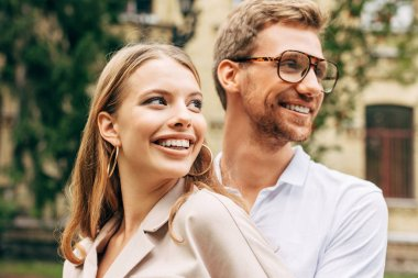 close-up portrait of smiling young couple in stylish clothes looking away