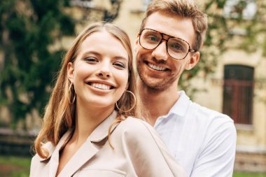 close-up portrait of smiling young couple in stylish clothes looking at camera