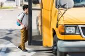 Fotografie side view of schoolboy entering school bus