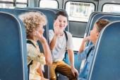 Fotografie Schülergruppe liebenswert geben hohe fünf zusammen während der Fahrt auf Schulbus