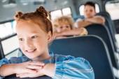 Fotografie Detailní portrét šťastná Malá školačka jízda na školní autobus se spolužáky za