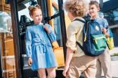 group of schoolchildren standing near school bus and talking