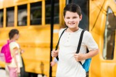 Glücklicher kleiner Schüler mit Rucksack steht vor Schulbus