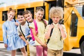 group of happy pupils looking at camera while standing in row in front of school bus