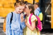 Photo cute little schoolgirls gossiping in front of school bus