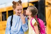 Photo adorable little schoolgirls gossiping in front of school bus
