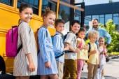 Fotografie queue of happy pupils standing near school bus with teacher