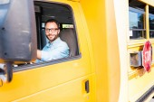 Fotografie atraktivní šťastný školního autobusu řidič při pohledu na fotoaparát
