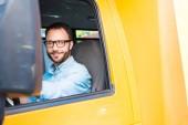 Fotografie hezký šťastný školního autobusu řidič při pohledu na fotoaparát
