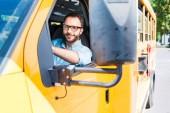 Fotografie krásný usměvavý řidič školního autobusu při pohledu na fotoaparát