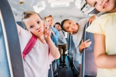 Fotografia group of happy schoolchildren riding on school bus and looking at camera