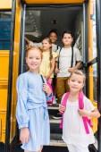 Fotografie group of adorable schoolchildren standing at school bus