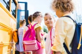Photo close-up shot of group of adorable schoolchildren standing near school bus