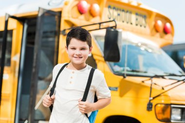smiling little schoolboy with backpack standing in front of school bus