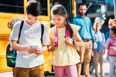 adorable schoolgirl and schoolboy using smartphone together in front of school bus with classmates