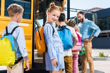 beautiful schoolgirl looking at camera while standing near school bus with classmates and teacher