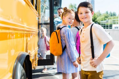 happy little pupils entering school bus with classmates